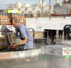 a driver for Reyes Holdings moves beer from a pallet while being overlaid on top of other photos of Chicago and employees in a warehouse