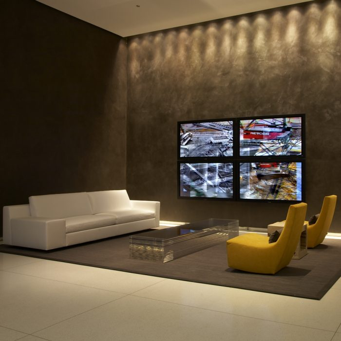 four tv screens in the center of a concrete lobby interior with artwork by Lincoln Schatz