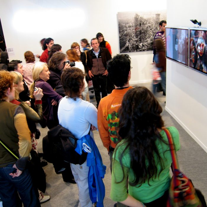 a large group of people look at two TV screens displaying an artwork by Lincoln Schatz installed on a wall in an art fair
