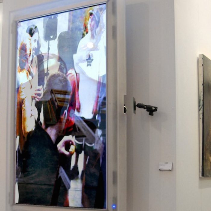 A vertically mounted HD monitor is attached to a column in an art fair booth at PULSE london showing a video artwork by Lincoln Schatz called Cluster