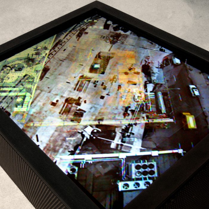 a computer screen is mounted into a black steel box and is sitting on the floor at a diagonal while multi-layered video footage of 600 North Fairbanks being built