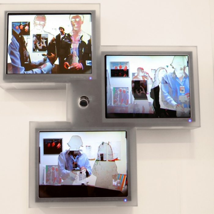 3 small computer screens show the artwork I, You, We, by Lincoln Schatz, the screens are framed in frosted in plexiglas with a small camera pointing from a hole in the center