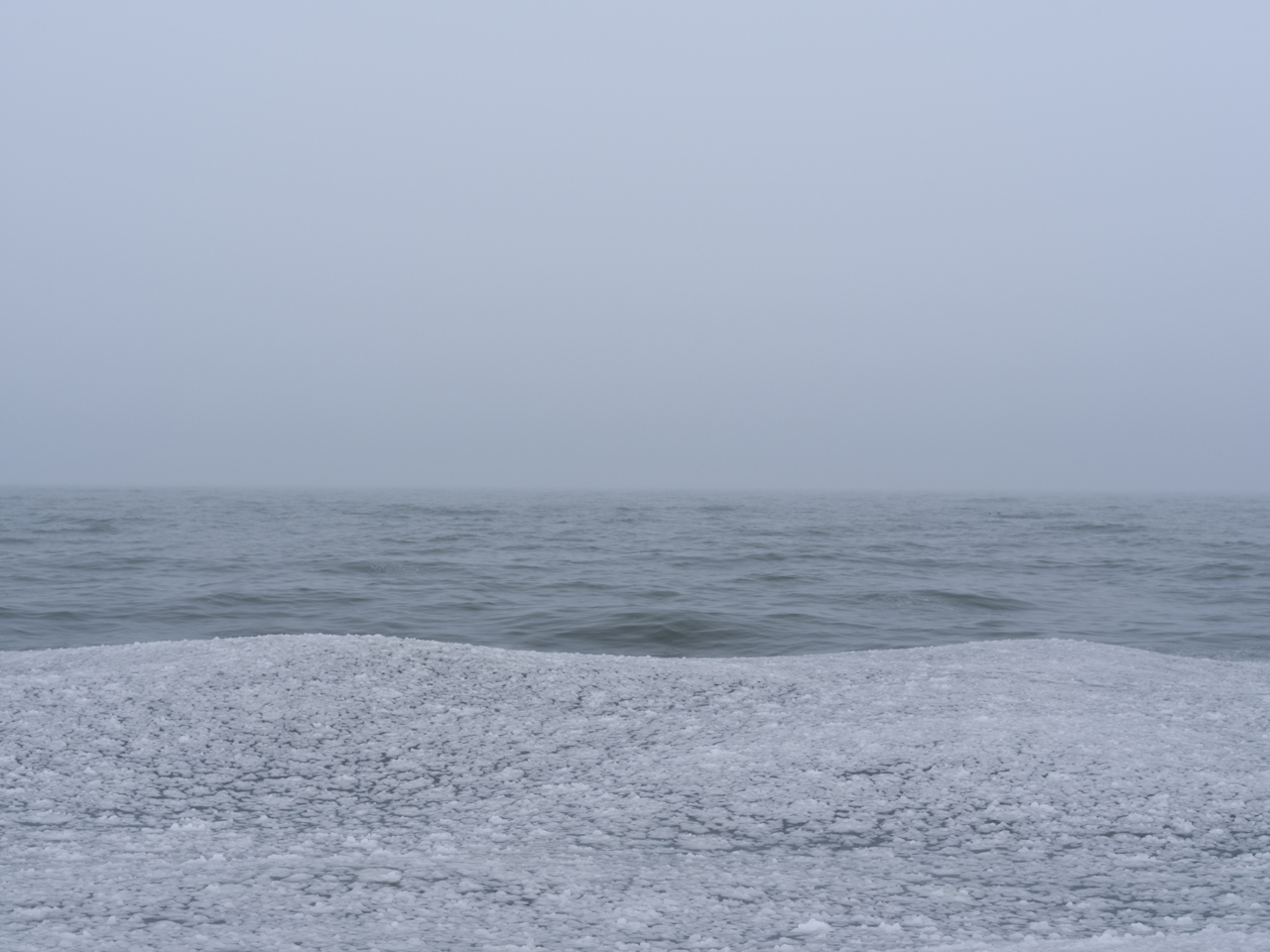 a bed of loose ice forms on a fog covered Lake Michigan