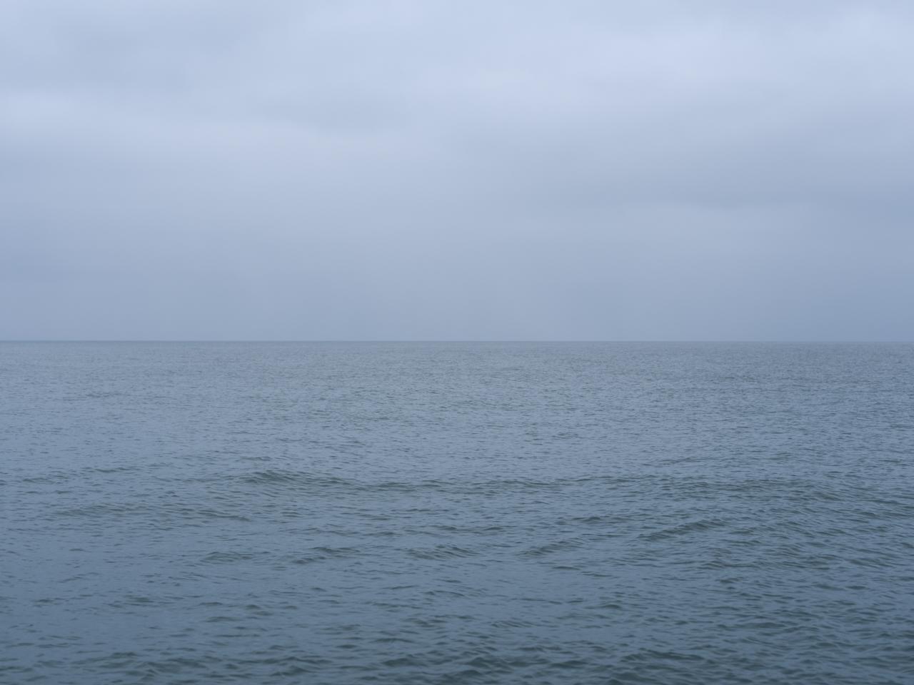 clouds and lake nearly match on a hazy blue day on Lake Michigan
