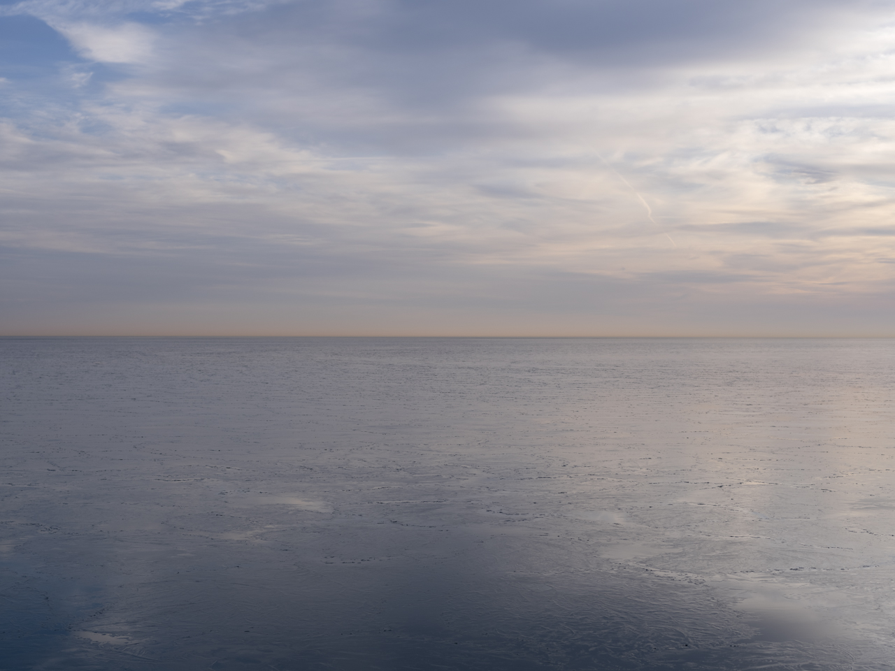 pastel blue skies with a yellow horizon on Lake Michigan