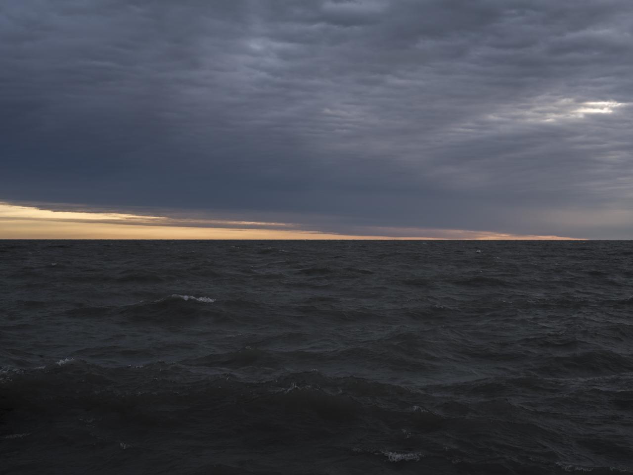 dark skies and water over Lake Michigan and a golden yellow horizon