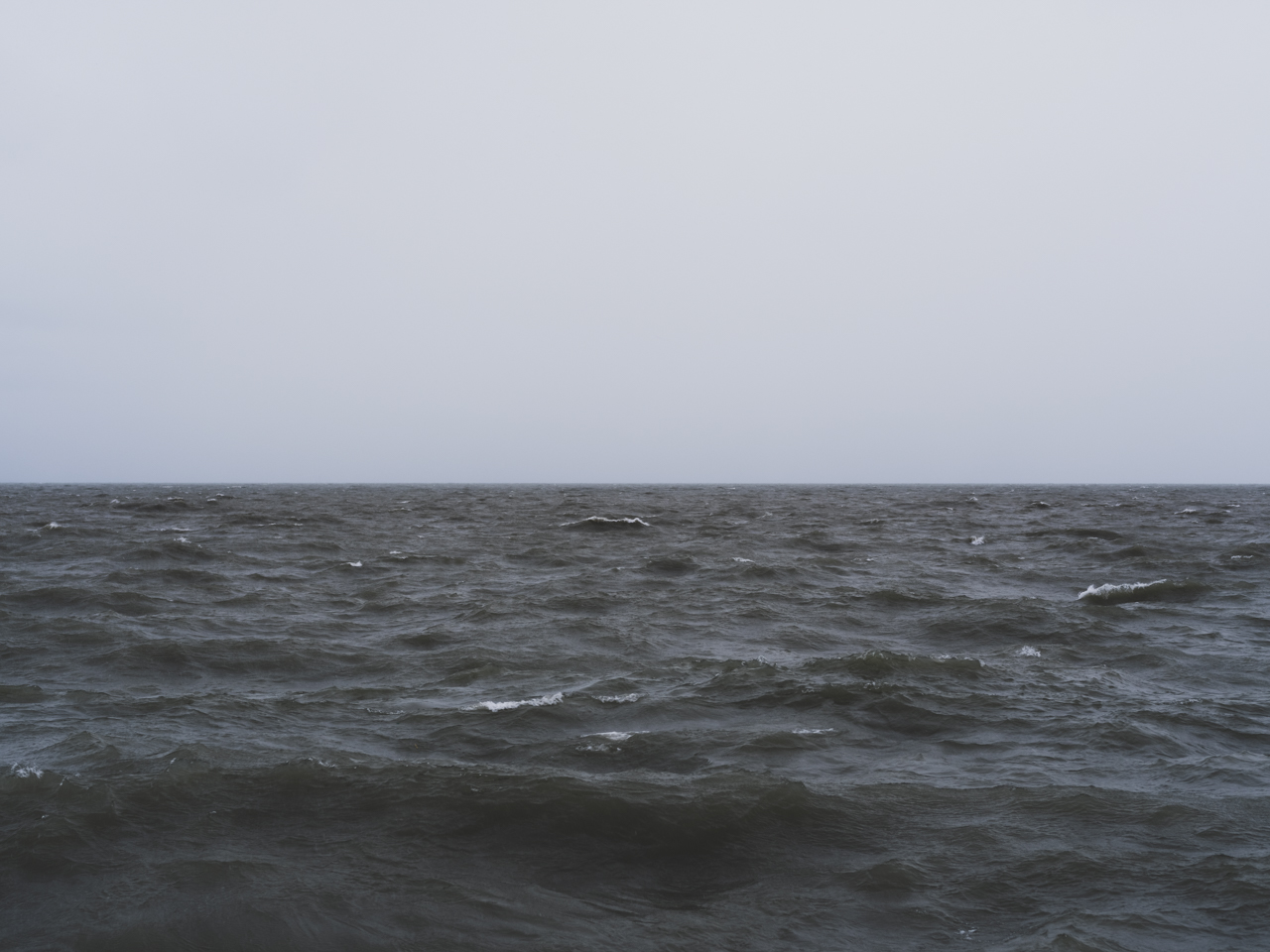 a still gray sky over large dark waves on Lake Michigan