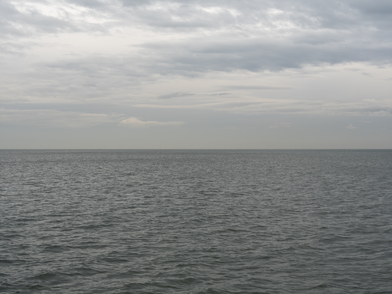 cloud cover is heavy in the sky with a slightly rippling surface of Lake Michigan