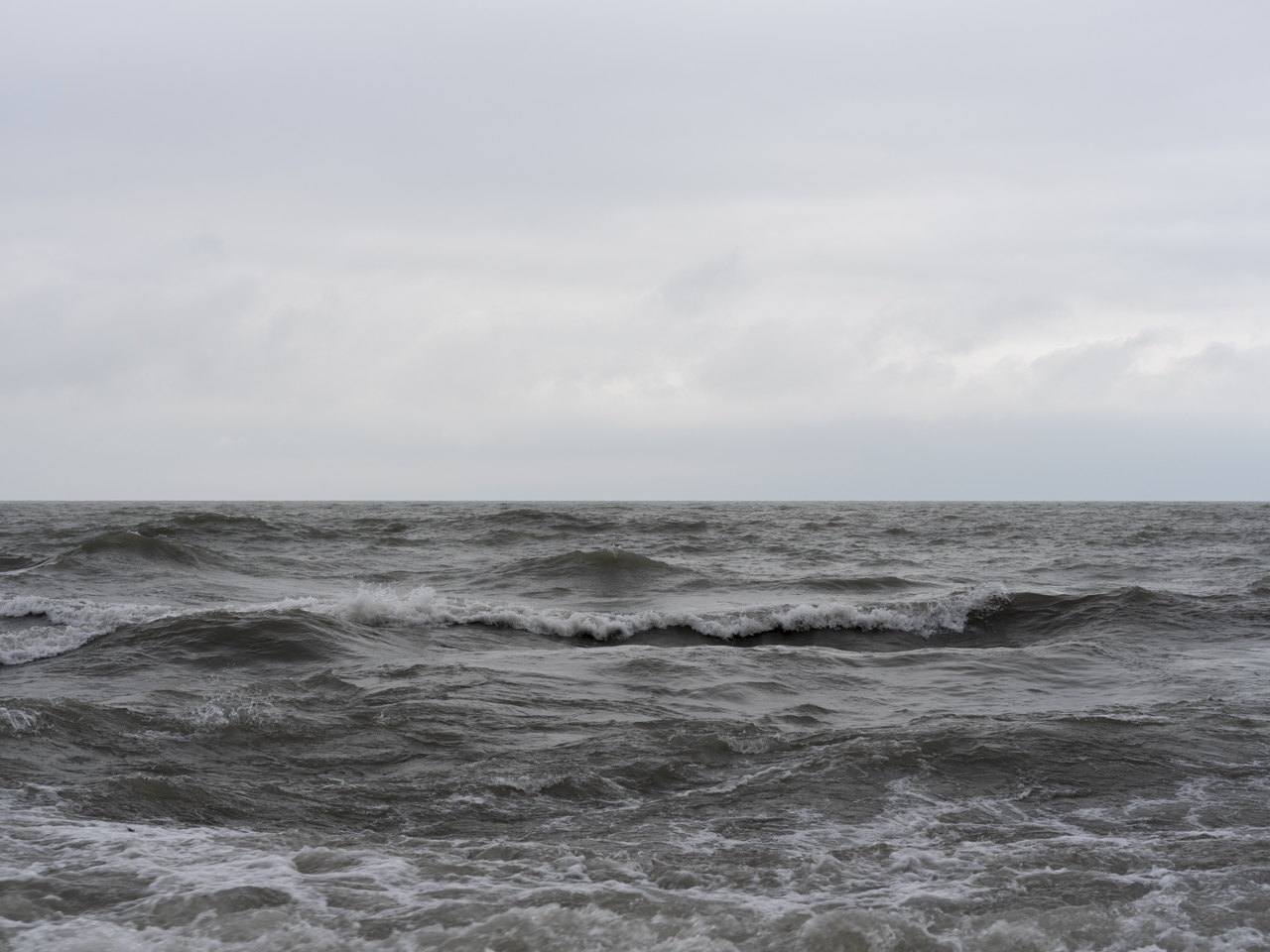 big rippling waves on lake michigan with whitecaps and heavy clouds in the sky