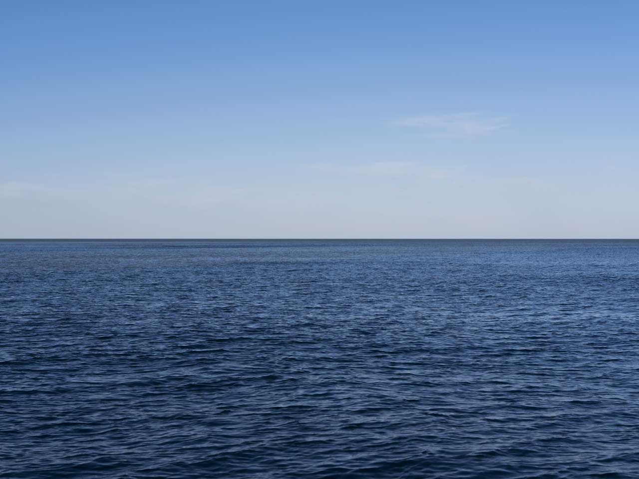 clear blue skies with whispy clouds on the horizon with slight rippling lake water