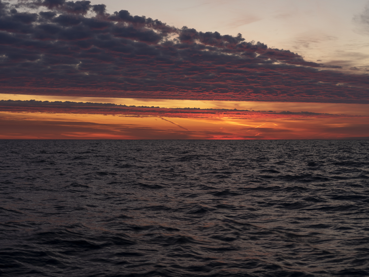 candy reds and yellows fill the skies over Lake Michigan