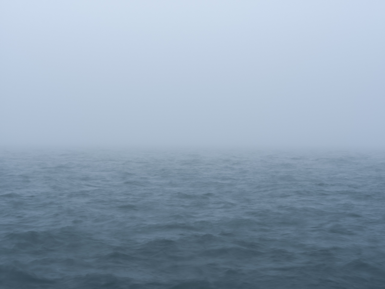 a heavy fog lies over the lake which is a particular color of blue
