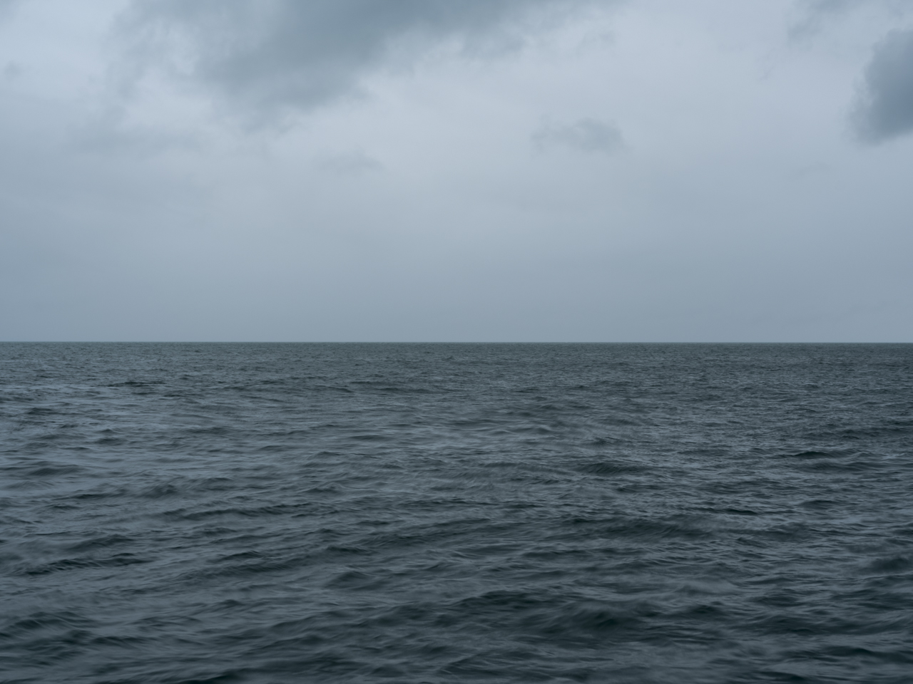 a darker day on Lake Michigan with heavy cloud cover and ominous water