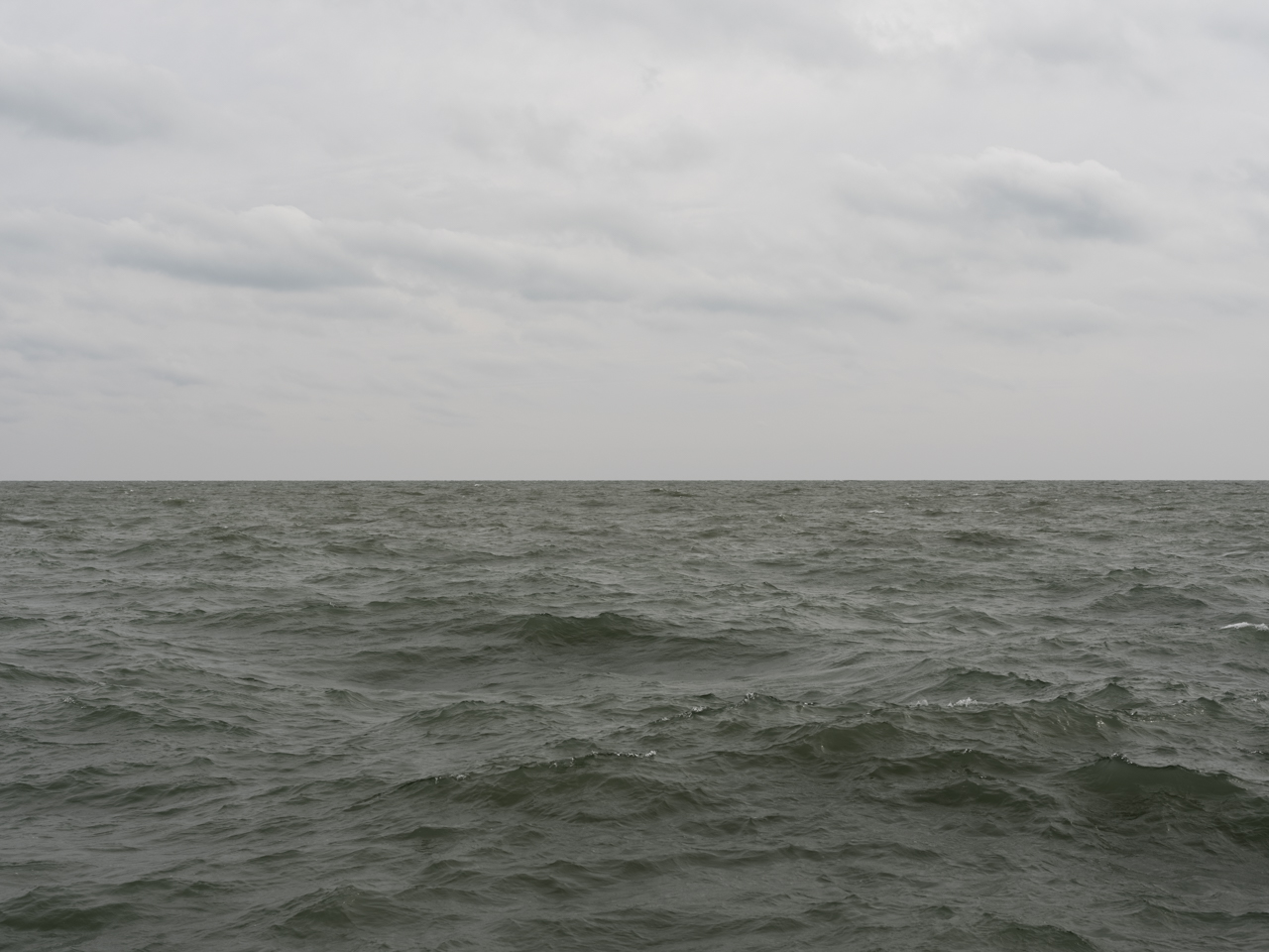 muted green waters of Lake Michigan with a cloudy gray sky