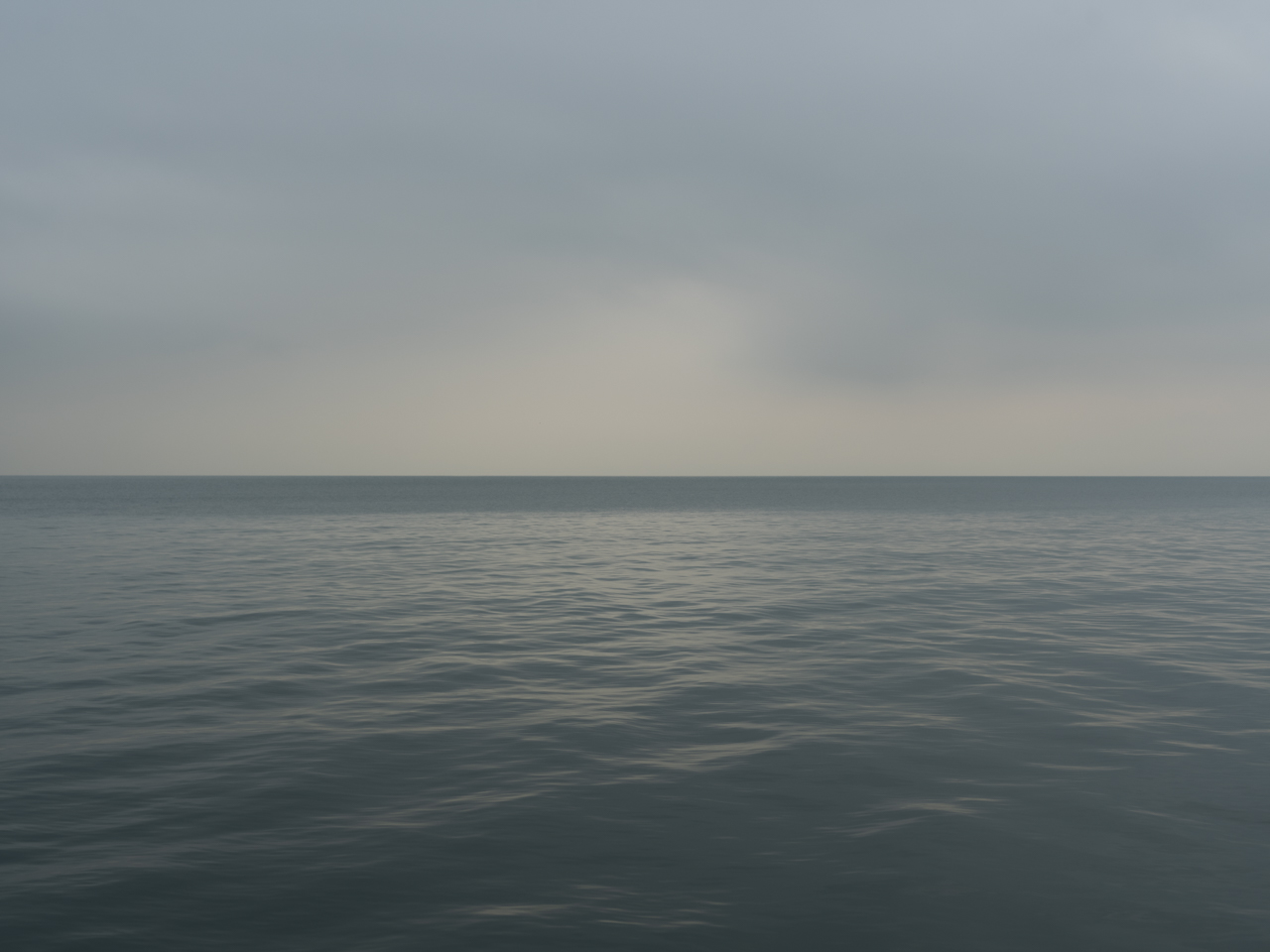 overcast blue and green day on Lake Michigan with light at the horizon