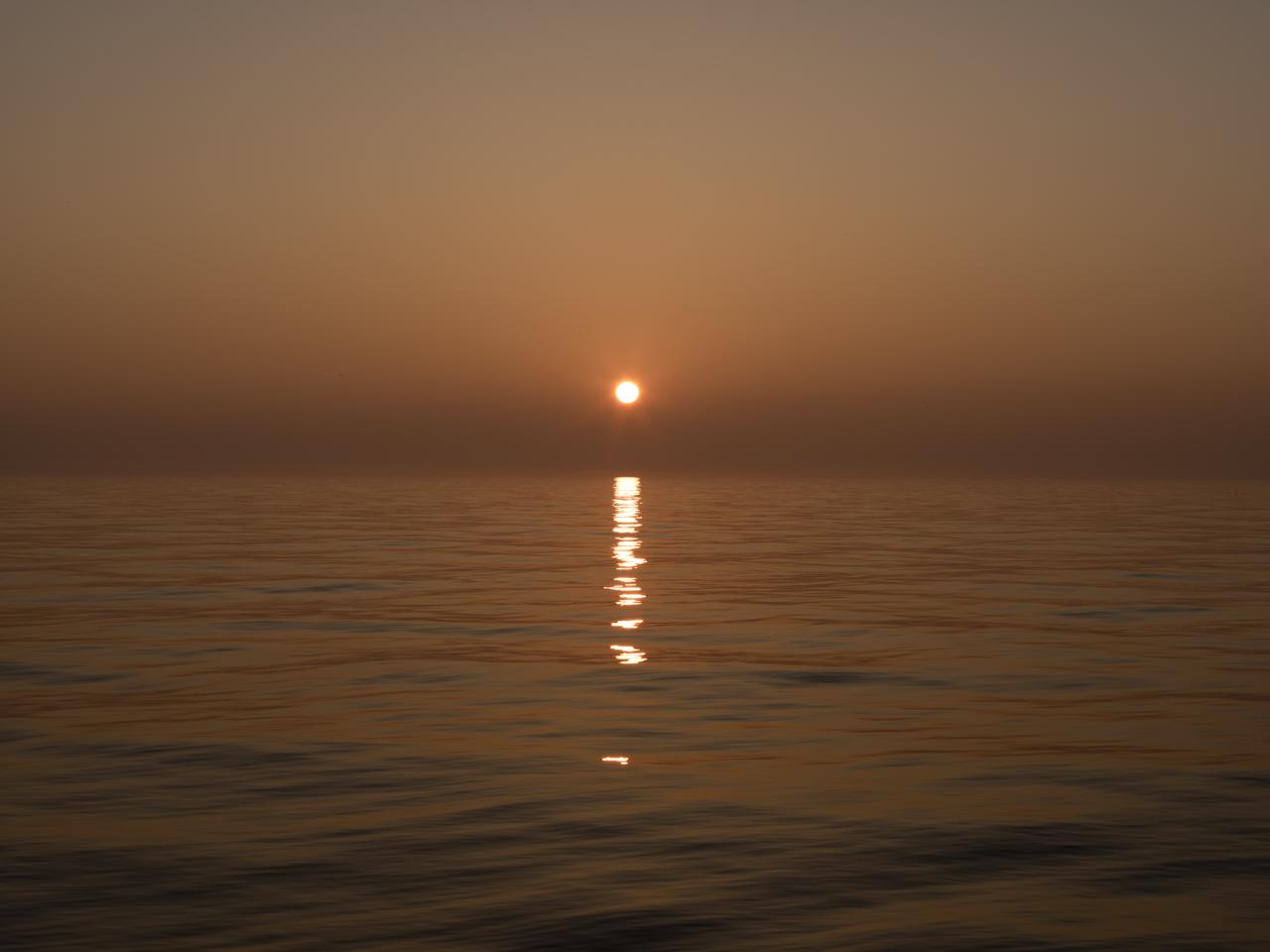 a sun rise in a bronze sky over Lake Michigan