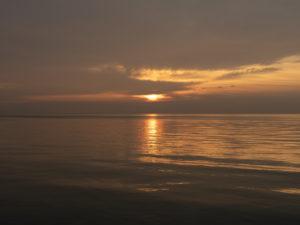 sun rise in a bronze sky, early morning on Lake Michigan