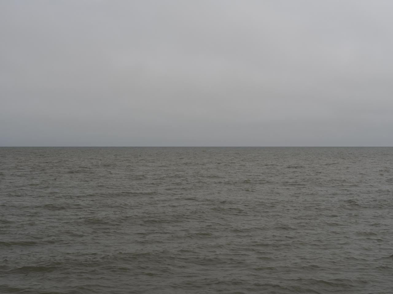 a slate gray sky over muddy green waters on Lake Michigan