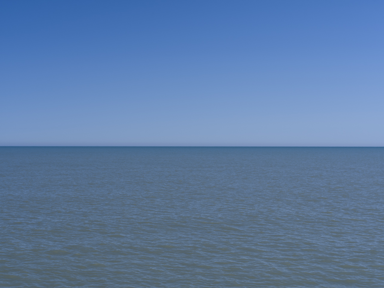 a blue day on Lake Michigan with no clouds in the sky