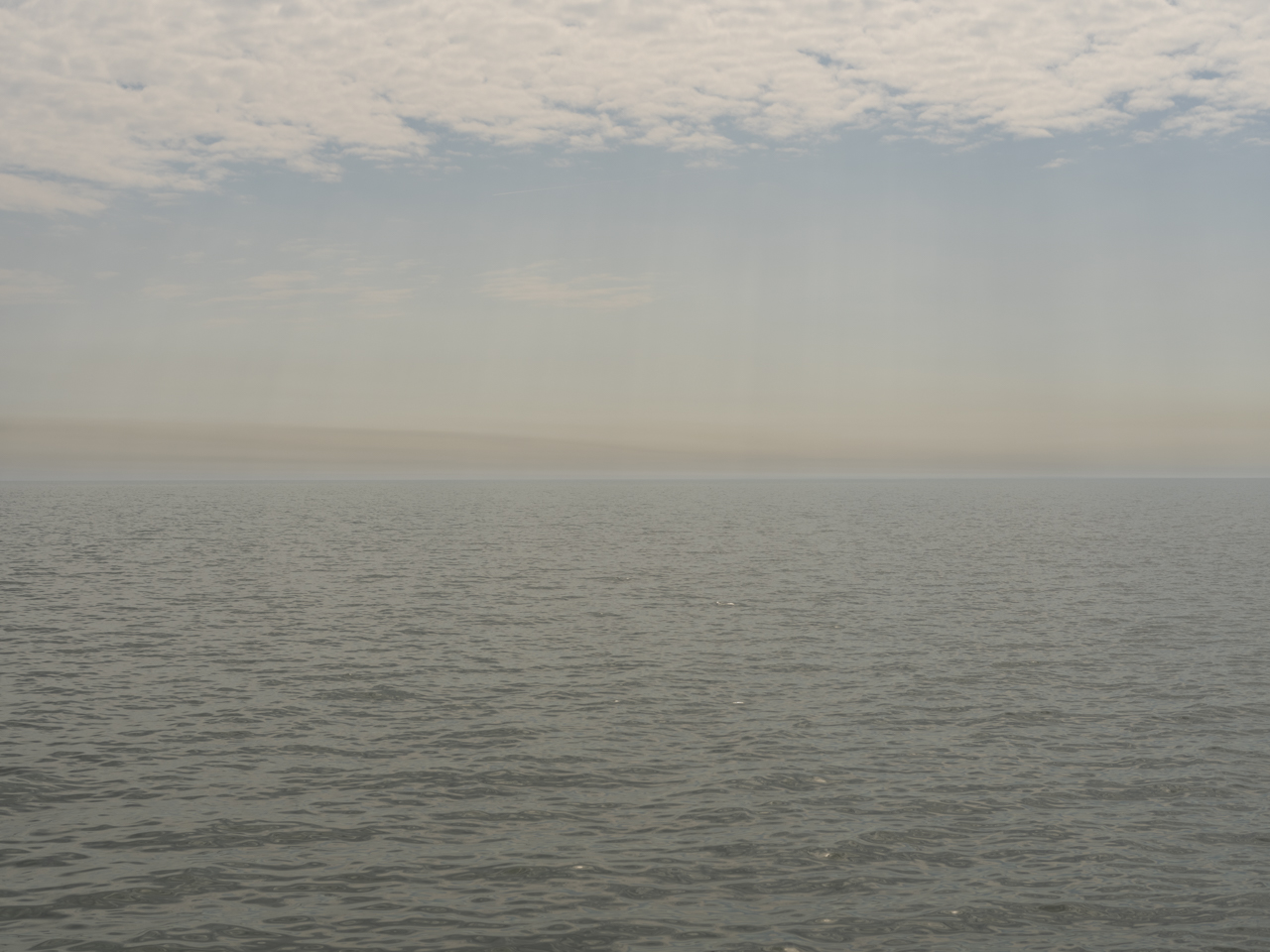 a green gray day on Lake Michigan with brown clouds in a hazy blue sky
