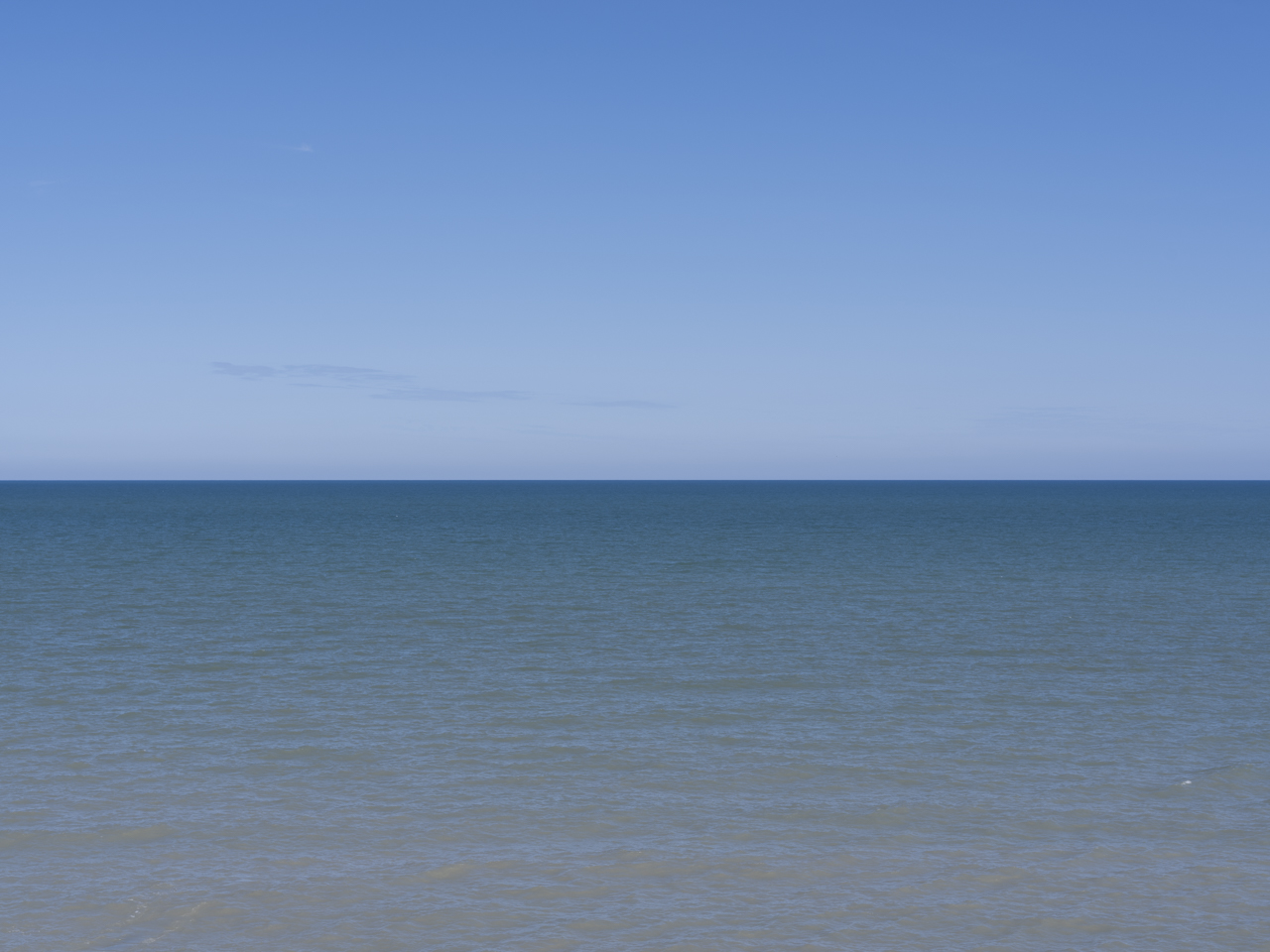 a clear blue day with waters of Lake Michigan in a brown to blue ombre