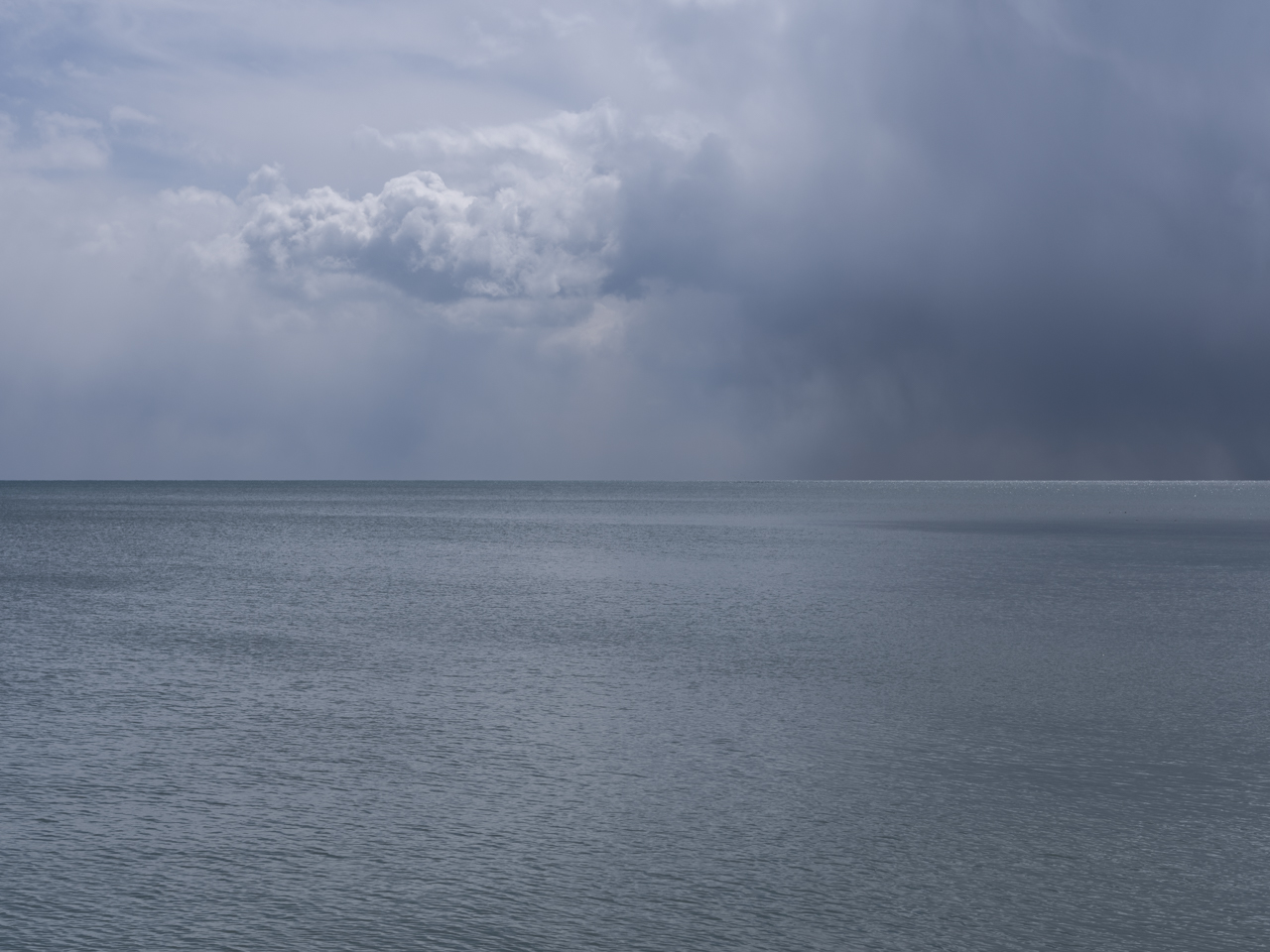 Clouds fill the sky as heavy darkness occludes the sky over a gray green Lake Michigan
