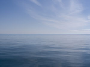 clouds wisp across the right half of this in this photo from the Lake Series, April, 2019, where the lake is a reflection of the sky above, it's deep blue waters, rolling only so slightly