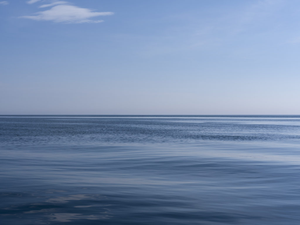 a smooth water day on Lake Michigan with an almost clear blue sky