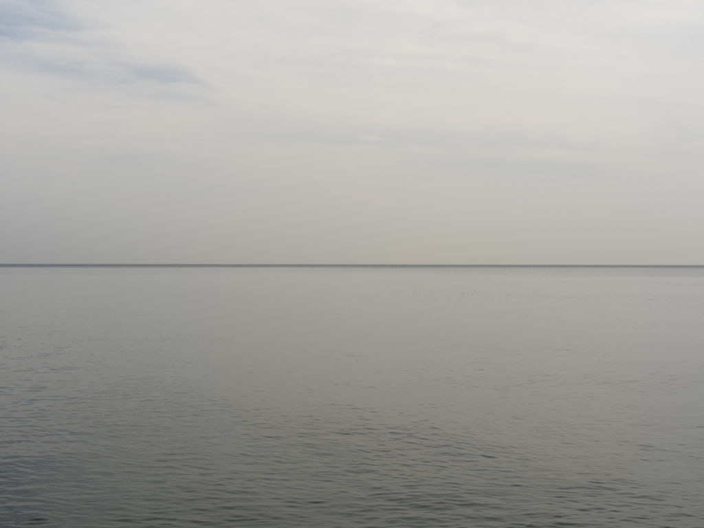 a flat gray day with almost no waves on Lake Michigan