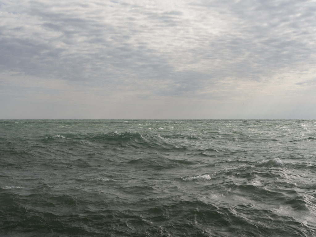 green waters with white caps on Lake Michigan and gray clouds