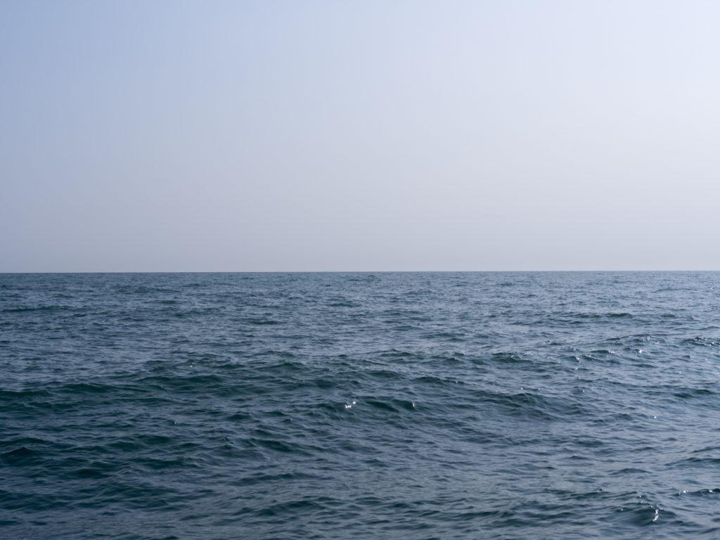 a clear blue sky and slight waves with a hazy sky