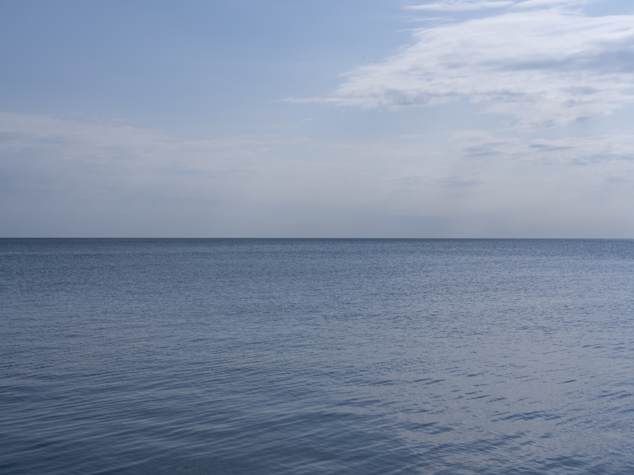 it almost appears like there is smoke on the horizon on a hazy blue day on Lake Michigan, clouds are thin and layered in the sky