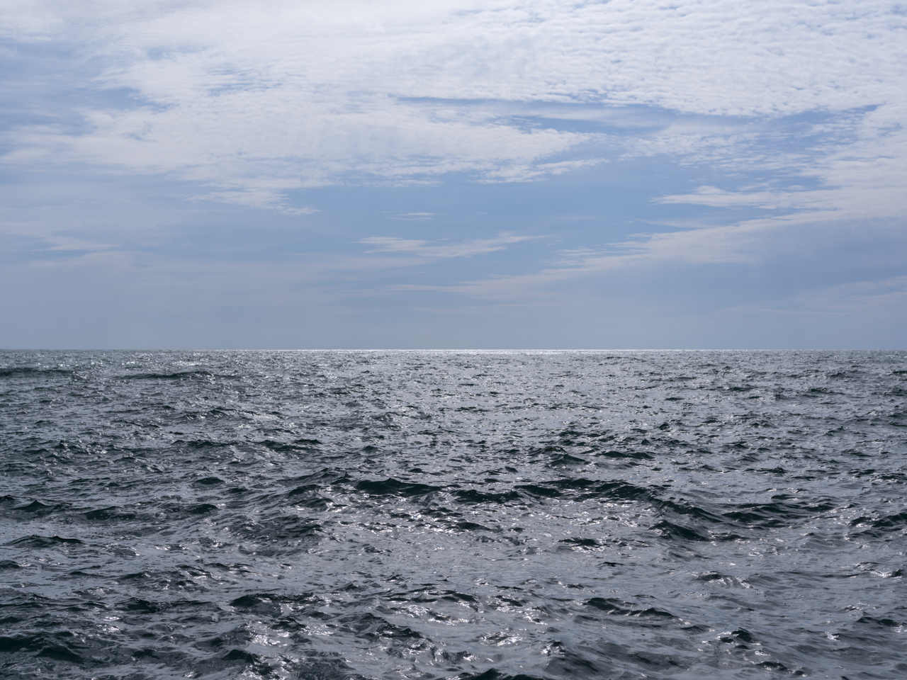 slate gray and blacks in the waters of Lake Michigan while thin lace-like clouds drape a blue sky