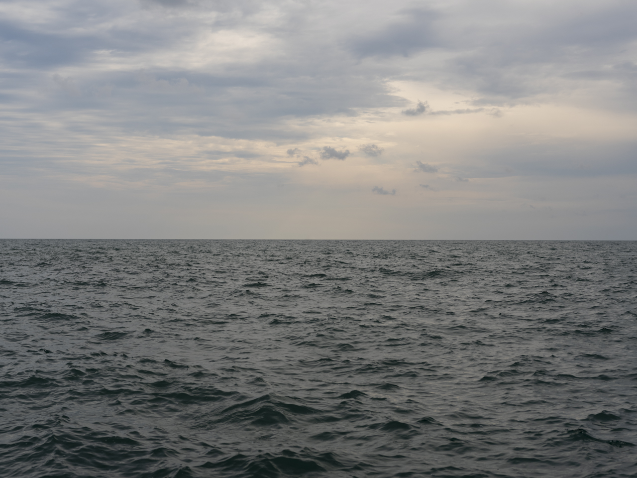 cloudy skies over green gray waters on lake michigan, subdued tones and a heaviness to the air