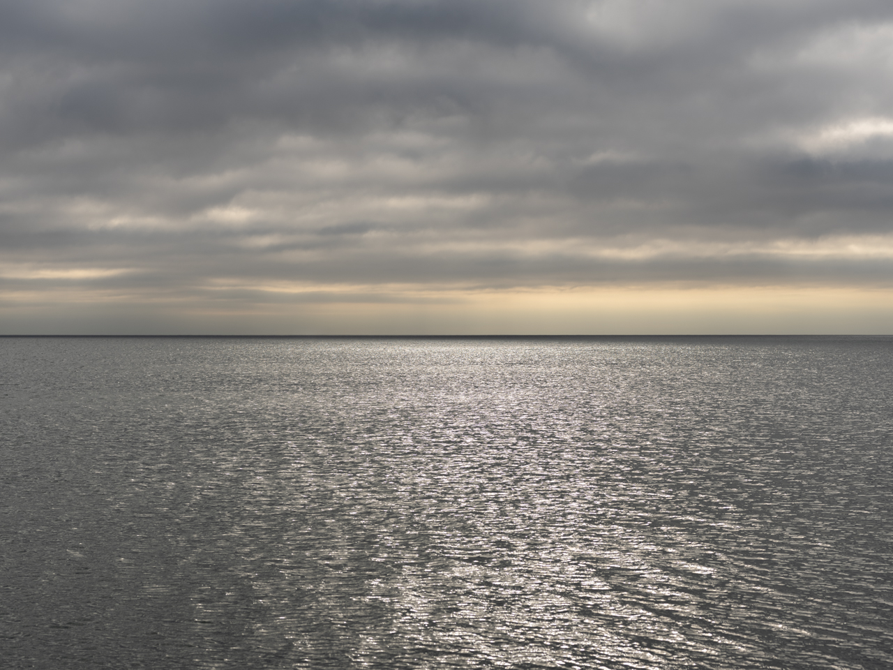 a cloudy sky over a silvery lake