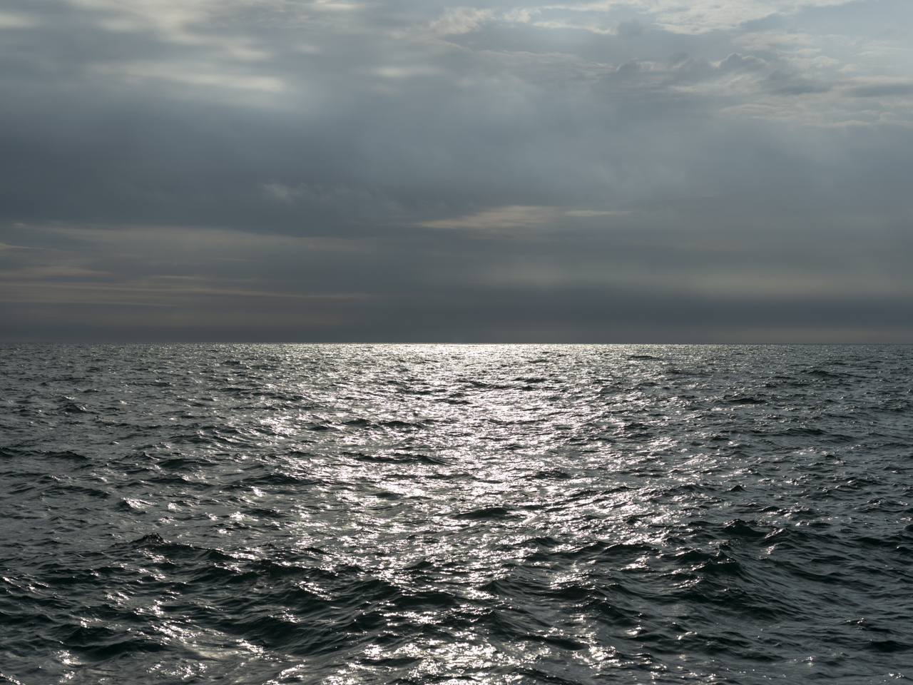 sunlight on a dark Lake Michigan with heavy cloud coverage