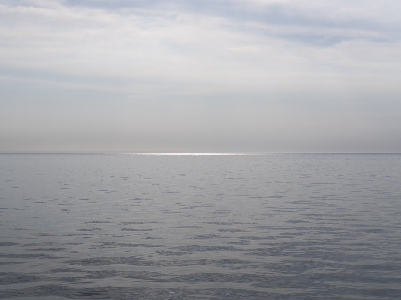 a sliver of light hits the water at the horizon of Lake Michigan