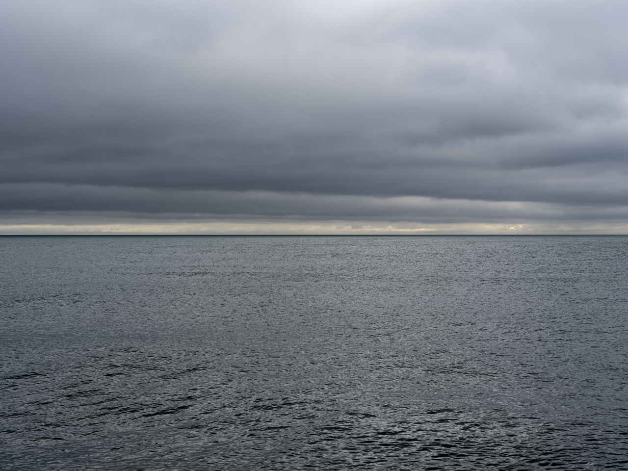 A gray day on Lake Michigan with heavy clouds and a sliver of light on the horizon