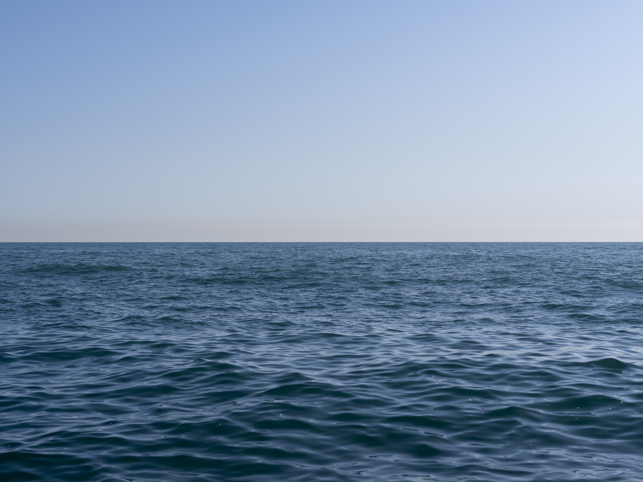 A light blue sky with deep blue waves on Lake Michigan