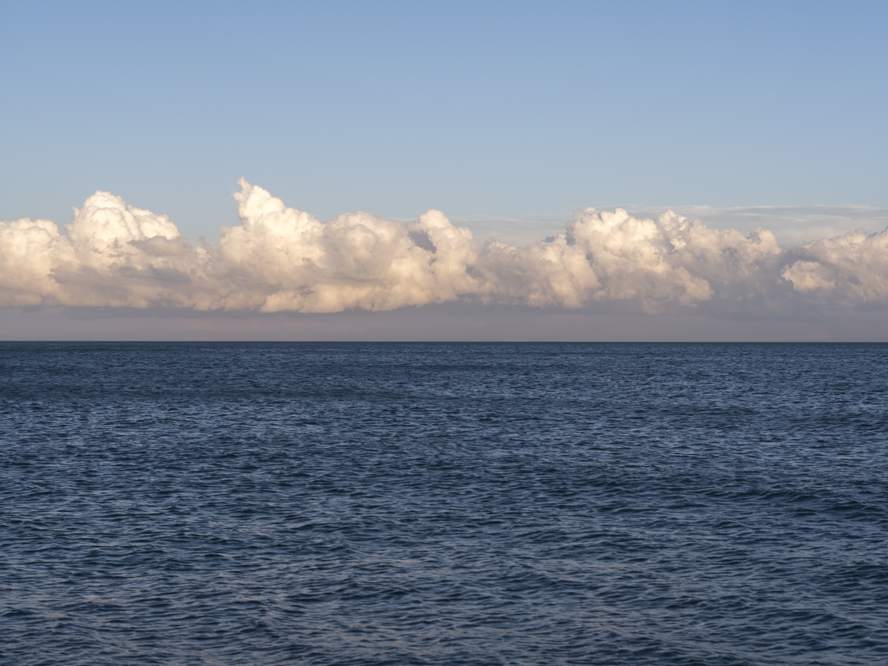a row of clouds above the horizon along Lake Michigan