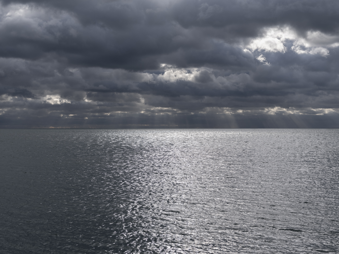 a dark sky with light streaming through over a steely Lake Michigan