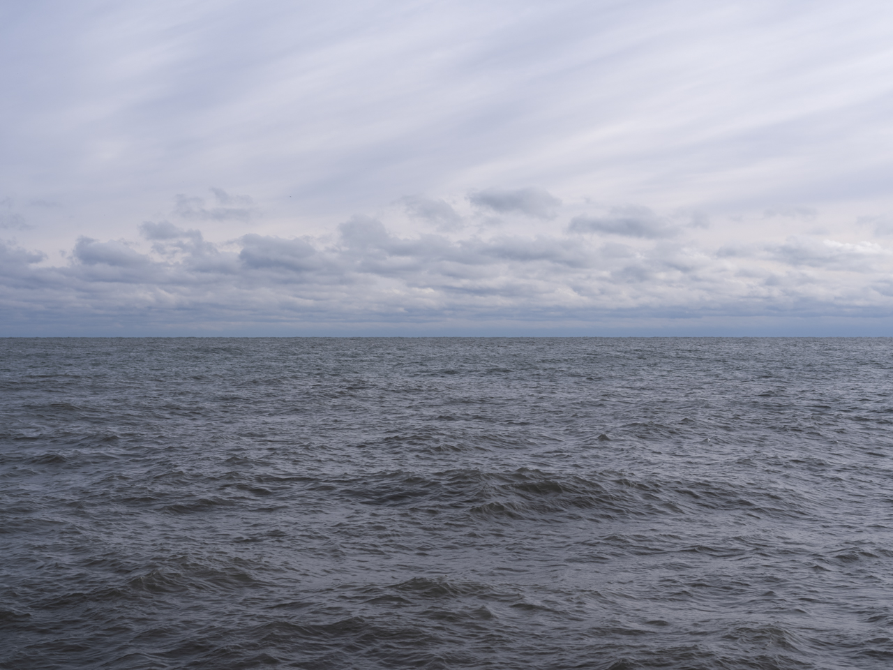 a cloudy day on lake michigan with blue tones and slight waves