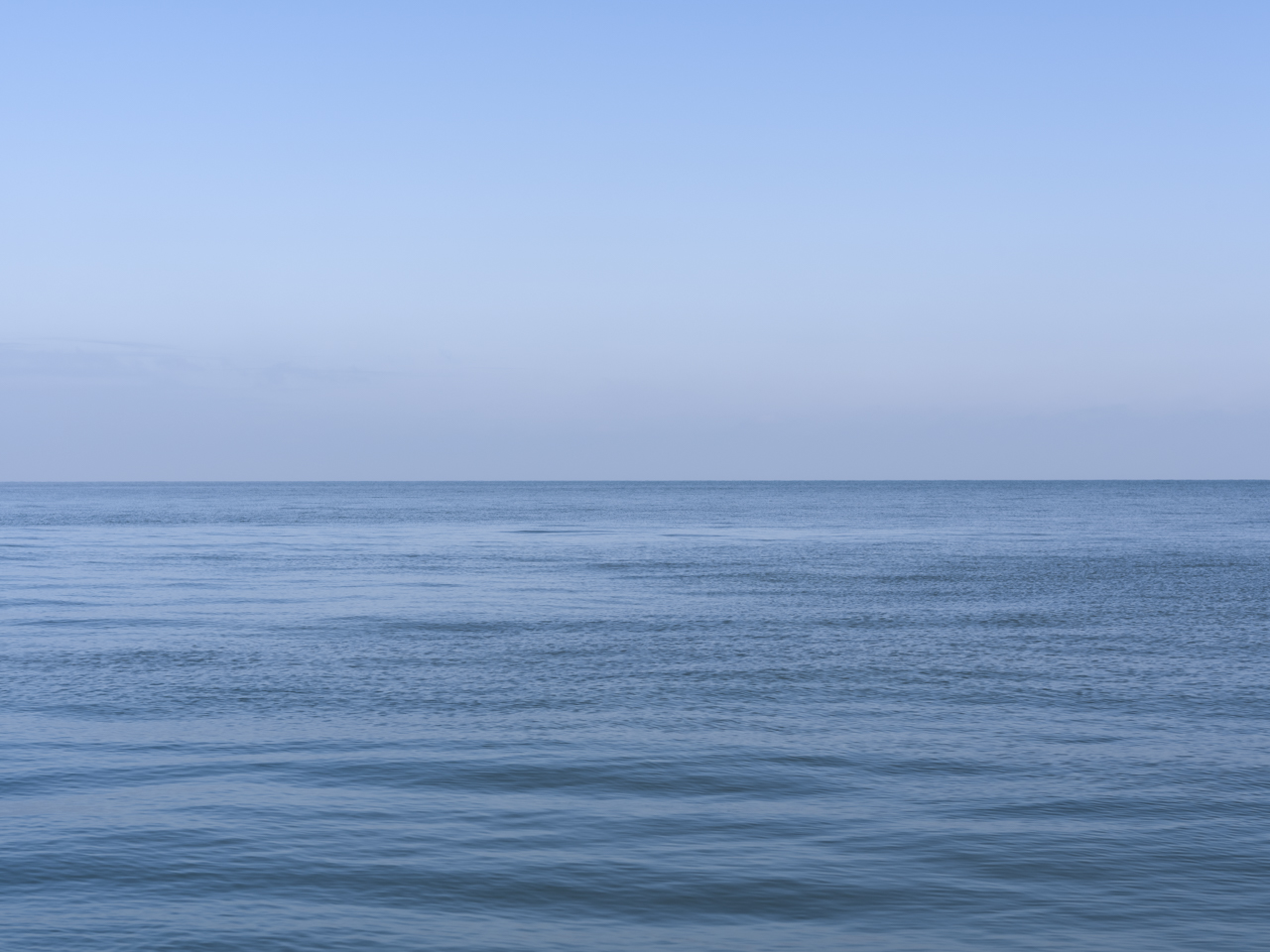 a perfect blue day with a light filled sky and barely any waves on Lake Michigan