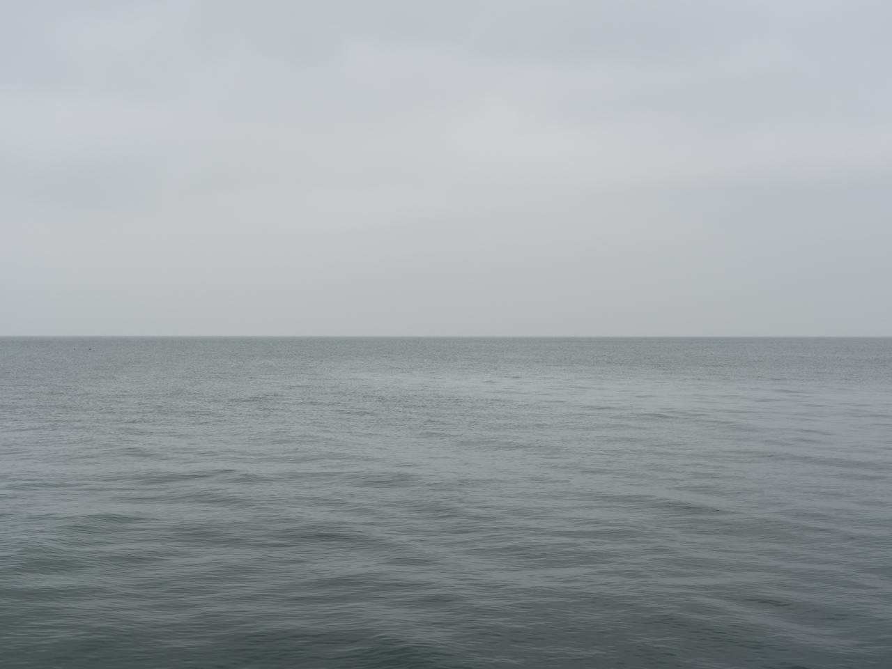 A gray morning on Lake Michigan with a gray green lake