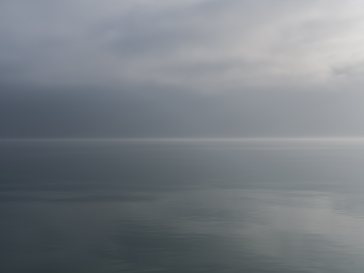 foggy and dense clouds cover a gray lake