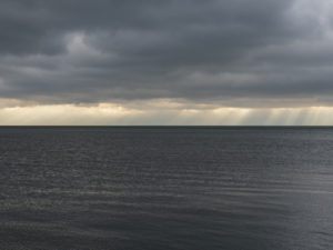dark lake water and rains on the horizon with dark and heavy clouds from the Lake Series, November 2019