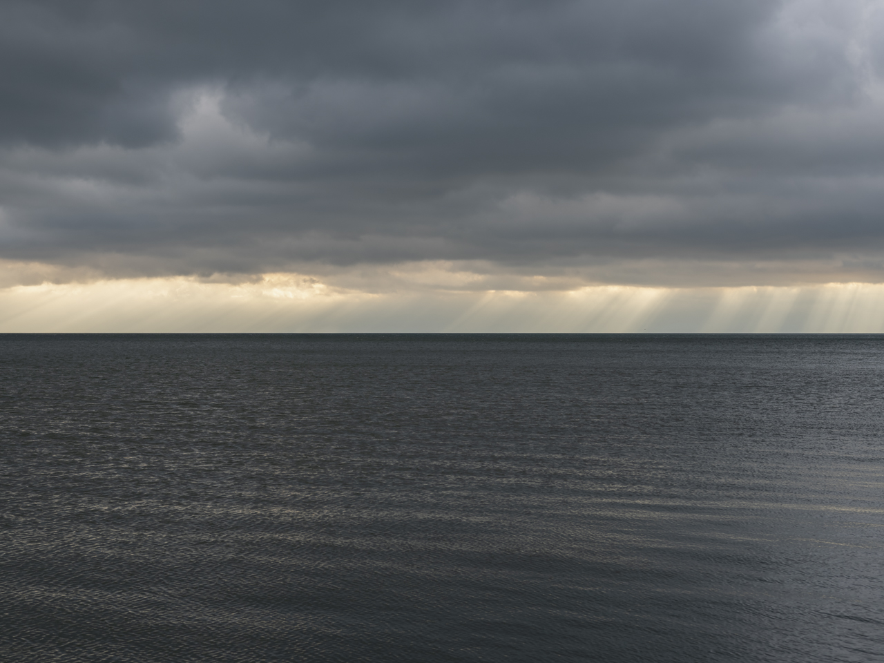 dark lake water and rains on the horizon with dark and heavy clouds
