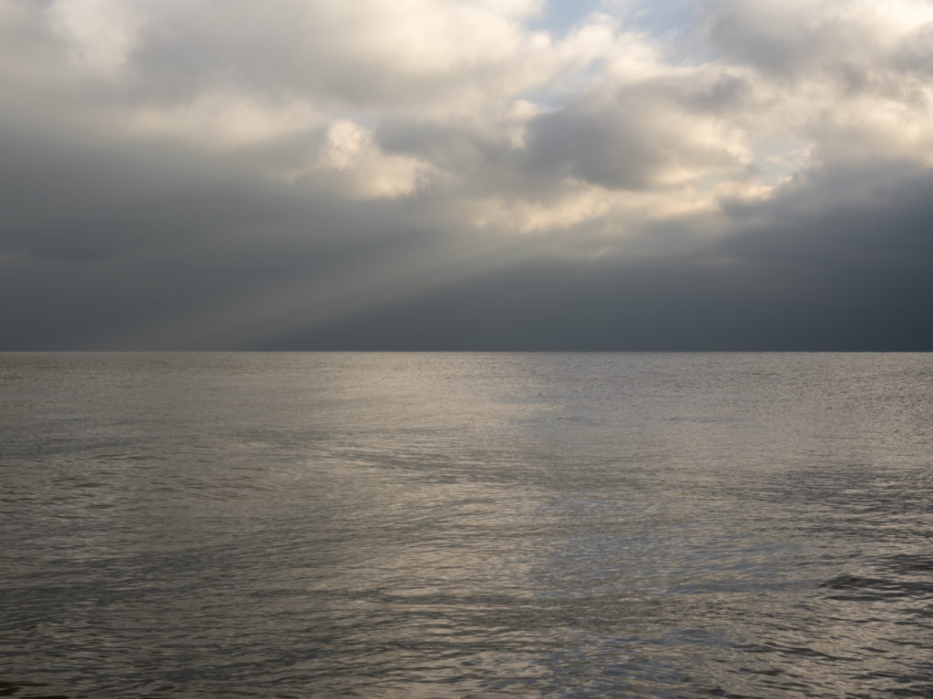 respite from the storm with sun cutting through clouds on Lake Michigan