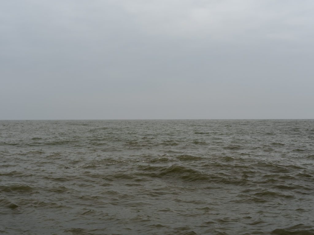 Flat, gray winter on Lake Michigan with greenish water and waves