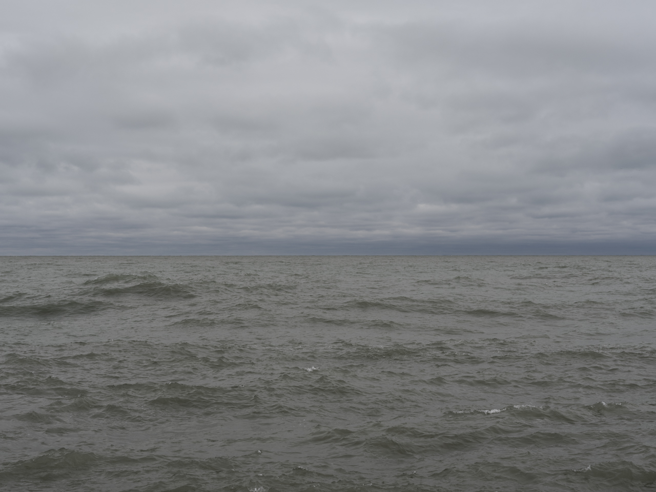 a very gray day on the lake where clouds are fully filling the sky overhead and the waters starting to pick up movment, the waves a green color